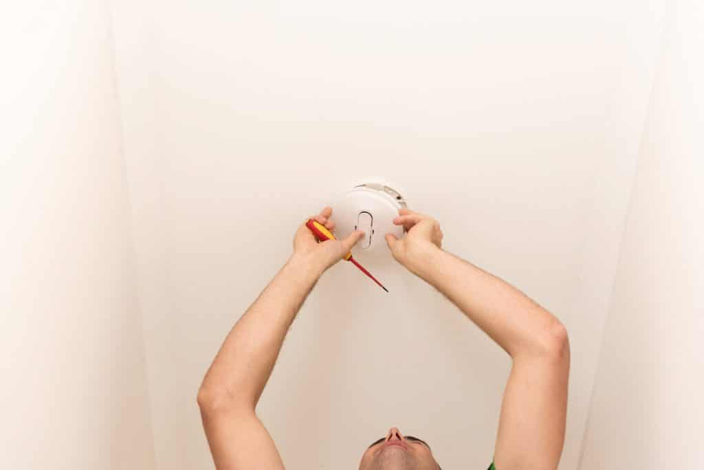 Electrician Working On A Smoke Alarm